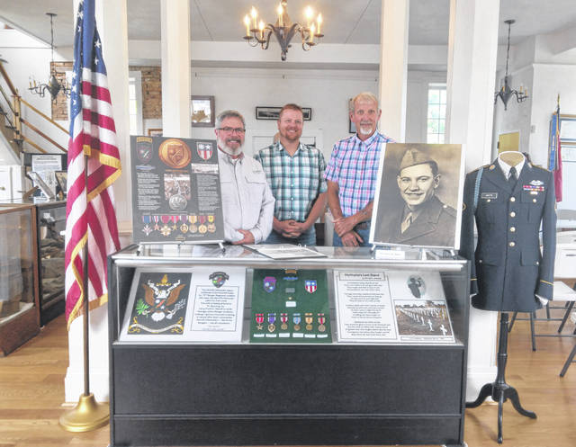 Commissioners Shannon Miller, Jimmy Will and Tim Ihle are pictured with the Army PFC James Wilmer White display at the Chester Courthouse.