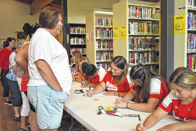 Fans of the Wahama White Falcon Softball Team stood in a line to get softballs and photos signed by each member at a reception in New Haven Tuesday.