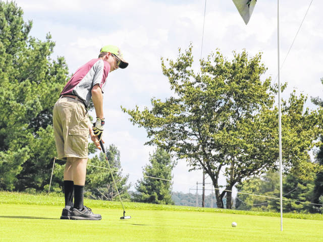 Meigs sophomore Landon McGee sinks a putt on the par-4 sixth hole, during a TVC Ohio match at the Meigs Golf Course in Pomeroy, Ohio.