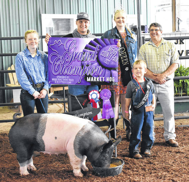 Jaycie Jordan (left) won Grand Champion Market Hog on Wednesday morning. Pictured with Jordan from left are Meigs County Fair King Jacob Spencer, Meigs County Fair Queen Olivia Harris, Little Mister Everett Lee and the hog show judge.