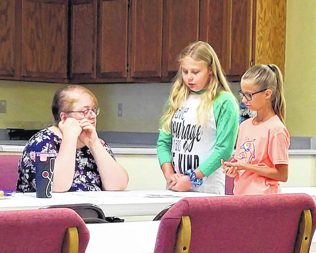 Caleigh Keyes and Zoey Kinder explain to Judge Elizabeth Lawrence about their troop group project.