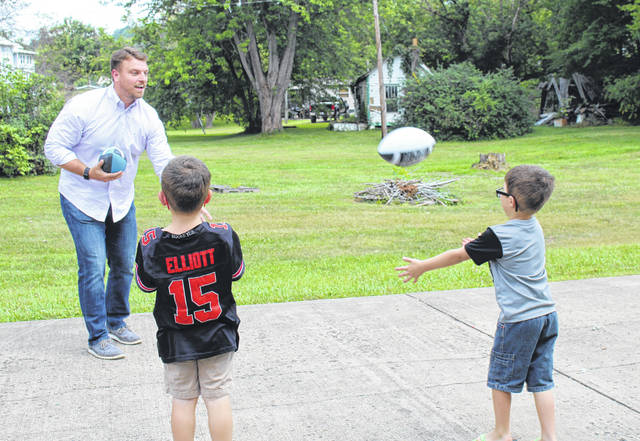 """State Rep. Jay Edwards tosses football with tow young children at the Children's Hunger Alliance food distribution on Monday. Kids were also given """"sport in a bag"""" items which included footballs, soccer balls and more."""