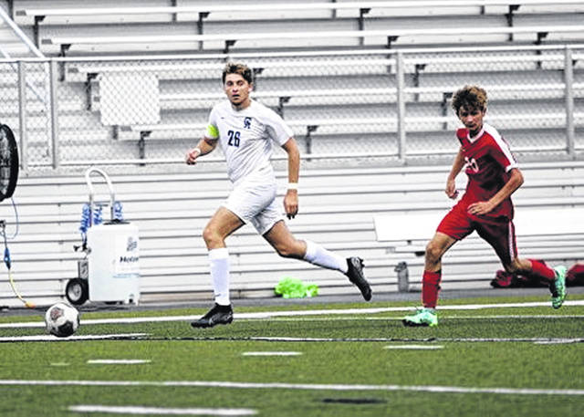 Gallia Academy senior Seth Nelson (28) tracks down a free ball and looks to deliver a crossing pass during Thursday night's boys soccer match against Jackson at Alumni Stadium in Jackson, Ohio.