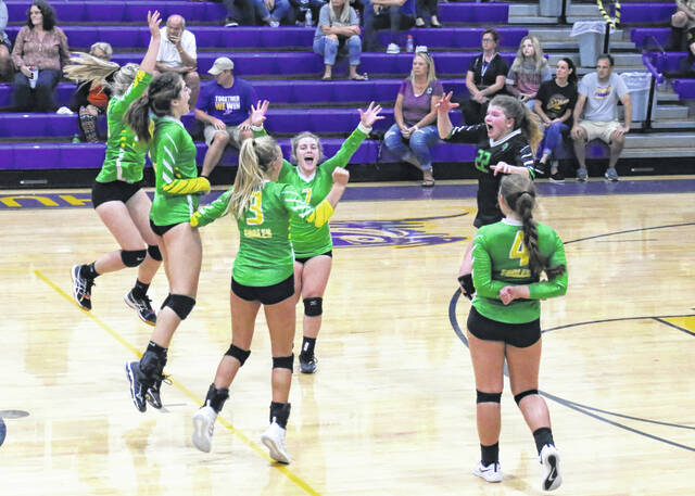 Members of the Eastern volleyball team celebrate the winning point of the match Tuesday night against Southern in Racine, Ohio.