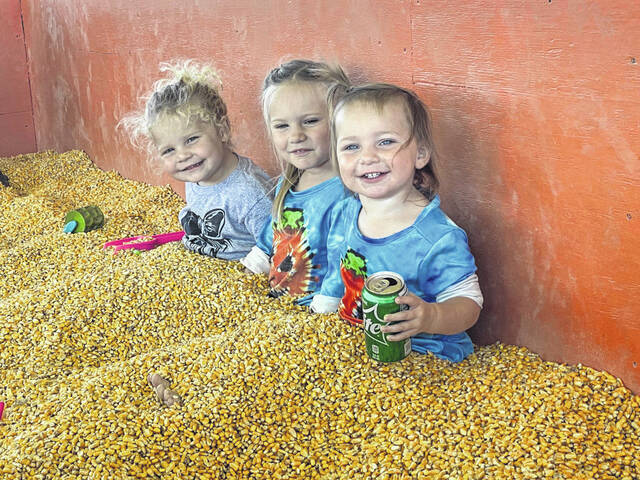 Emma Vollborn, Macey and Miley Jarrell play in the corn pit, one of the favorite activities at the farm.