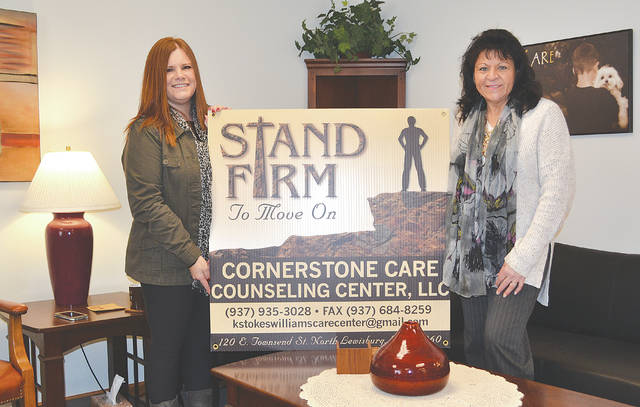 Cornerstone Care Counseling Center owner Kim Stokes-Williams, right, and psychiatric and mental health practitioner student Christine Boysel, left, hold a sign for the new counseling center inside the office.
