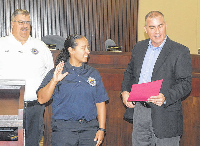 Mya Mitchell, Vandalia's new full-time firefighter/paramedic is administered the oath of office by City Manager Jon Crusey as Fire Chief Chad Follick looks on.