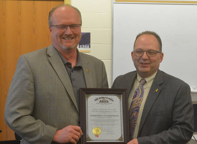 Auditor of State West Regional Liaison Joe Braden (left) presented the Auditor of State Award with Distinction to Vandalia-Butler City Schools Treasurer Eric Beavers during the Board of Education meeting on Tuesday.