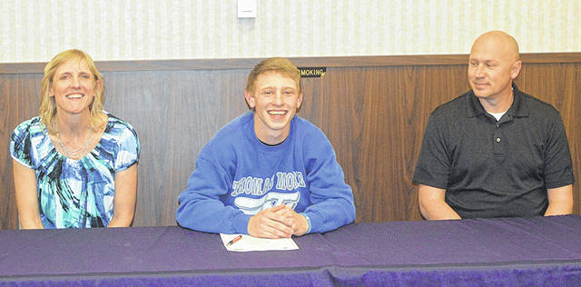 Butler basketball standout Kort Justice (center) signed a National Letter of Intent to play basketball at Thomas More College on Friday. He is pictured with his parents Tammy and Greg.