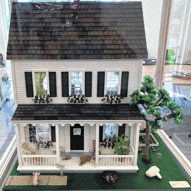 A spider web with a special message, a cradle and baby high up in a tree, a tiny carpet bag and umbrella… these are just a few of the literary references visitors may find in the Storybook Dollhouse, on display now at the Vandalia Branch of the Dayton Metro Library, 330 S. Dixie Drive.