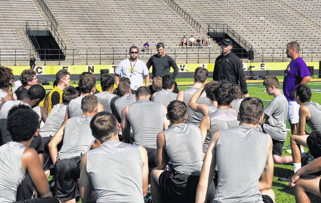 Centerville football coach Brent Ullery (left) and Butler football coach John Puckett (right) address the Elk and Aviator football teams after a joint practice and 7-on-7 competition on Wednesday morning at Centerville Stadium.