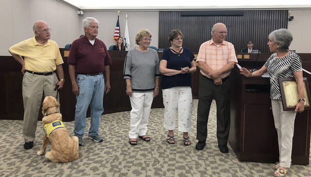 "Vandalia Mayor Arlene Setzer (right) presented a proclamation declaring Pollinator Week to members of the Historical Society of Vandalia-Butler (left to right) Foster ""Bud"" Brown with K-9 Companion trainee Camille, Al Tuttle, Mary Geiger, Jennie Dranschak, and Joe Dranschak."