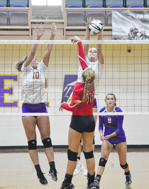 Grace Marshall (10) and Alyssa Burley (right) go up for a block versus Piqua on Tuesday.