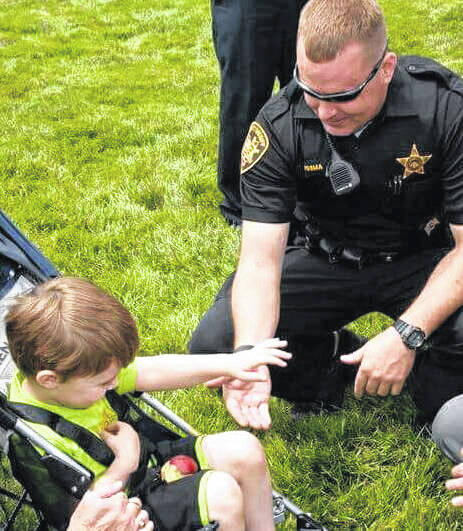 Deputy David Posma interacting with underprivileged child.
