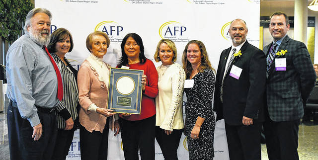 Smith Middle School students and staff were recognized for being Outstanding Youth in Philanthropy for ages 5-17 by the Dayton chapter of the Association of Fundraising Professionals. Pictured left to right are John Schmidt, Denise Palen, Marilyn Slusser, Rose Chinn, Kim Imwalle, Renee Cope, Ryan Rogers, and Rob O'Leary.