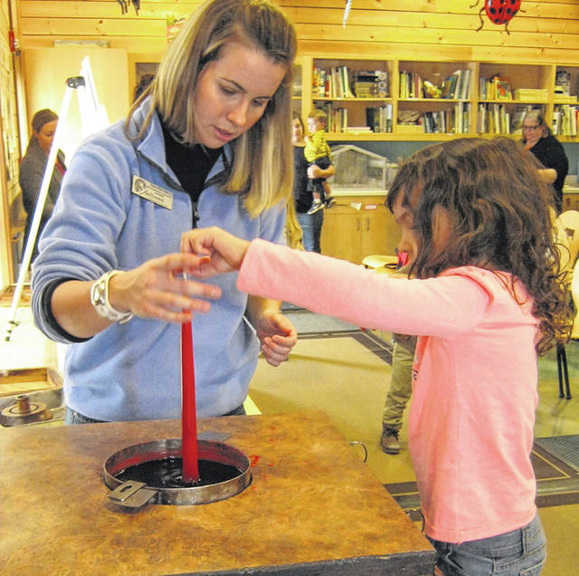 Traditional candle dipping using beeswax creates special memories at Aullwood in December.