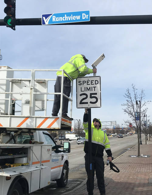 Vandalia Public Works employees install lighted speed limit signs on National Road in anticipation of the speed limit being reduced to 25 miles per hour between Ranchview Drive and Dixie Drive. The change takes effect Saturday, March 2.