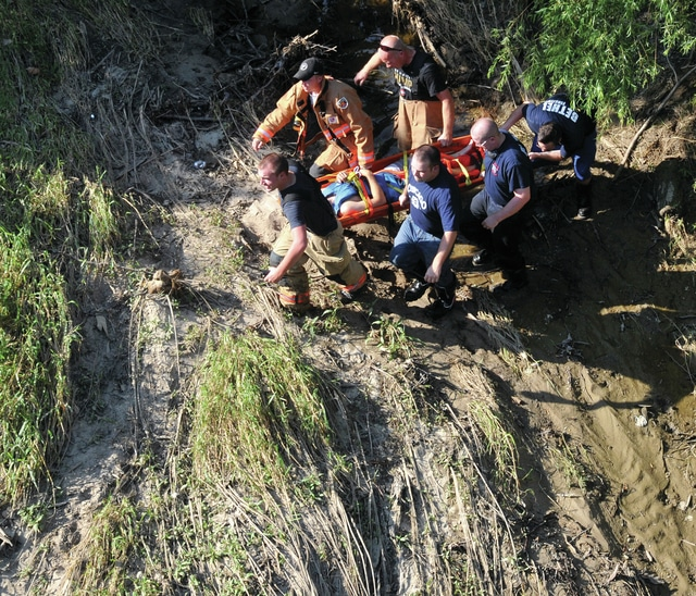 Mike Ullery | Daily Call Firefighters and medics from Bethel Township and Tipp City carry a man away from the Great Miami River along St. Rt. 571 near Tipp City, to a waiting ambulance on Saturday afternoon.