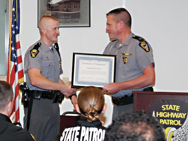 Mike Ullery | Daily Call Trooper Eric Devers of the Piqua Post of the Ohio State Highway Patrol is recognized for his life-saving efforts following a crash on I-75 on April 28, 2015 during a ceremony at the Piqua Post/District 5 Headquarters on Thursday. Captain Dan Lay of District 5 is presenting the certificate.