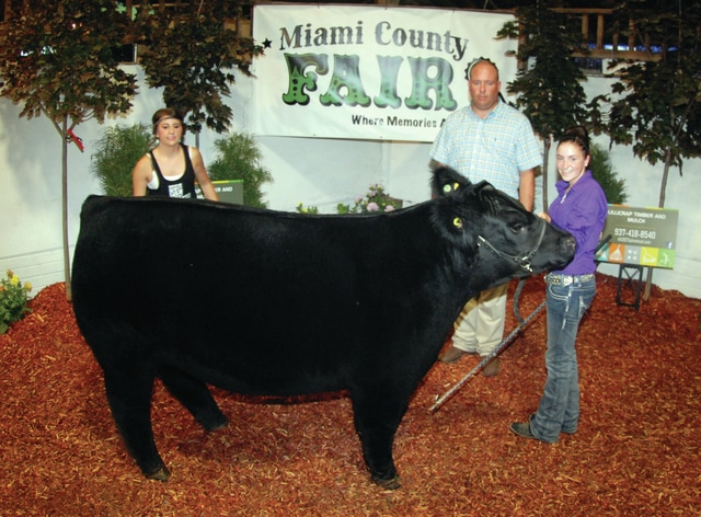 Kassidy Thompson, right, of Troy, won Grand Champion Market Steer. She is pictured with her sister Kaitlyn and beef show judge Gary Staley of Urbana.