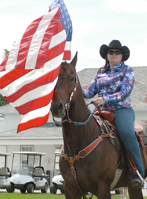 Anthony Weber | Troy Daily News Crystal Ganger of Future Horsemen of Miami County presents the colors during the opening ceremonies at the 2015 Miami County Fair on Friday in Troy.