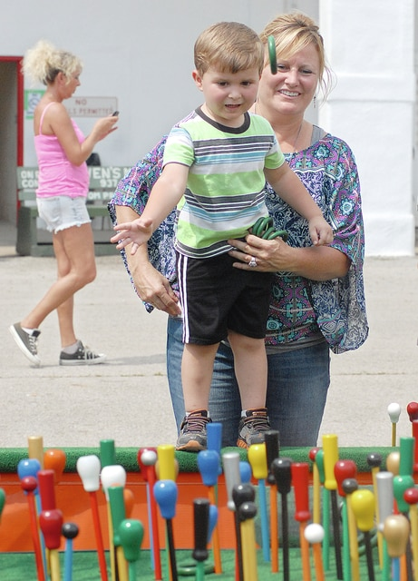 Anthony Weber | Troy Daily News Jennifer Henley helps balance Liam Baldwin, 3, while tossing rings at the Dearwester Canes cane game Monday at the Miami County Fair.