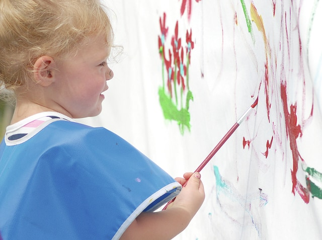 Anthony Weber | Troy Daily News Alianne Geus, 2, adds color to a Kids Day banner sponsored by the Miami County Fair board Monday at the Miami County Fair. Her mother, Cierra Geus, said the event was a good way to spend time together with the kids.