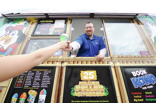Anthony Weber | Troy Daily News Allen Lay from Kona Ice of Troy hands out a tropical shaved ice treat Wednesday while visiting downtown Troy.