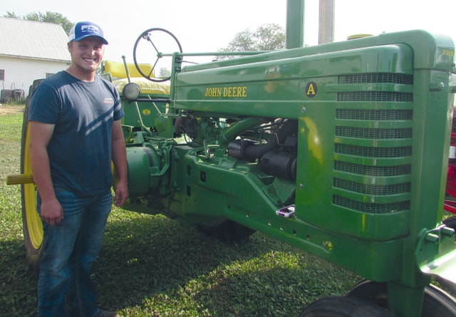 Melanie Yingst | Troy Daily News Brady Anderson, 18, of Troy, stands with this year's fair project, a 1951 John Deere A.