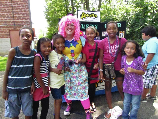 Provided photo Student receiving school supplies from the Third annual Back to School Bash pose with a clown entertainer during the event.