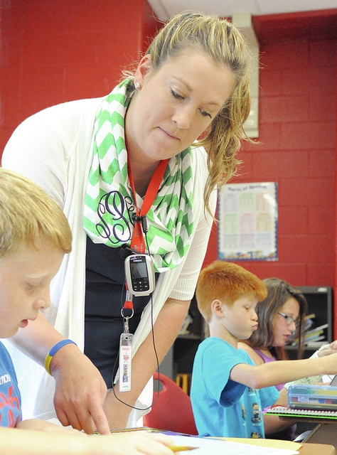 Anthony Weber | Troy Daily News Fourth-grade teacher Sarah Pacher helps students in a lesson on latitude and longitude during social studies recently at Forest Elementary School in Troy.