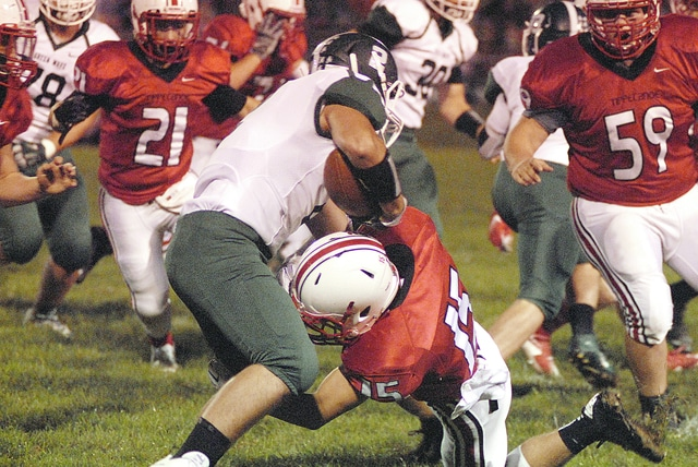 Anthony Weber/Troy Daily News Tippecanoe's Cade Rogers (15) tackles Greenville's Codi Byrd during Friday night's game at Tipp City Park.