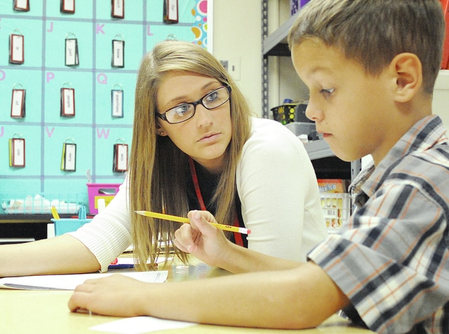 Anthony Weber | Troy Daily News Heywood Elementary School Intervention Specialist Mara Siegel works on spelling with students, including Haydin Arnold, Thursday at the school.