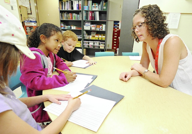 Anthony Weber | Troy Daily News Kyle Elementary School Title 1 reading teacher Aimee Winteregg works with Nevaeh Bragg, Jadyn Cushberry, center, and Isaac Henderson while writing sentences Friday at the school.