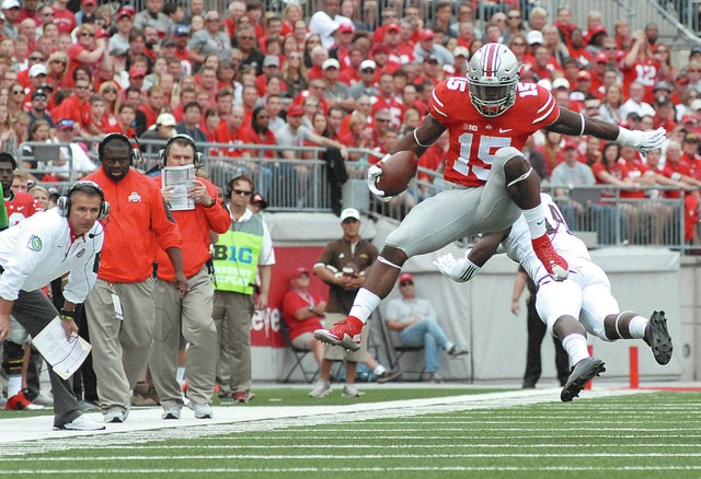 Anthony Weber   Troy Daily News Ohio State's Ezekiel Elliott (15) hurdles over a Western Michigan player as coach Urban Meyer looks on from the sideline Saturday at Ohio Stadium.