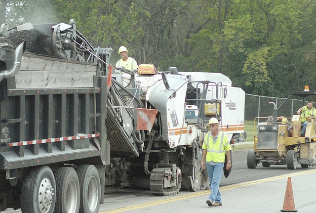 Anthony Weber | Troy Daily News Crews continue resurfacing work on Adams Street on Tuesday in Troy. The work may cause delays in the area for the next several days.