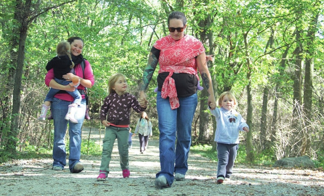 With her five-month-old daughter Fiona taking a ride on her back, Amy Brittingham, center, of Covington, hikes with her children Kinley (left), 4, and Bear (right), 2, as part of the Trailing Moms & Tots program funded by the Miami County Parks District. Mothers or caregivers can bring children ages 0-5 years hiking along the trail at the Charleston Falls Preserve with the group, bringing social opportunities for families and a connection to nature.