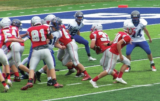 Submitted Photo Troy freshman football team quarterback Jacob Adams (10) hands off to Garrett Jones (32) while the offensive line blocks against Xenia.