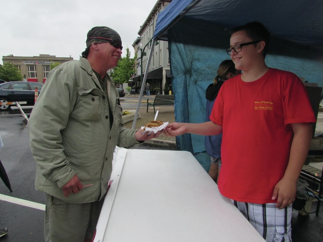 Allison C. Gallagher | Troy Daily News Cameron Ferguson hands an order of jambalaya to Herk Lonnon at Taste of Troy. Ferguson worked for Ducky's Snowballs and Ice Cream.