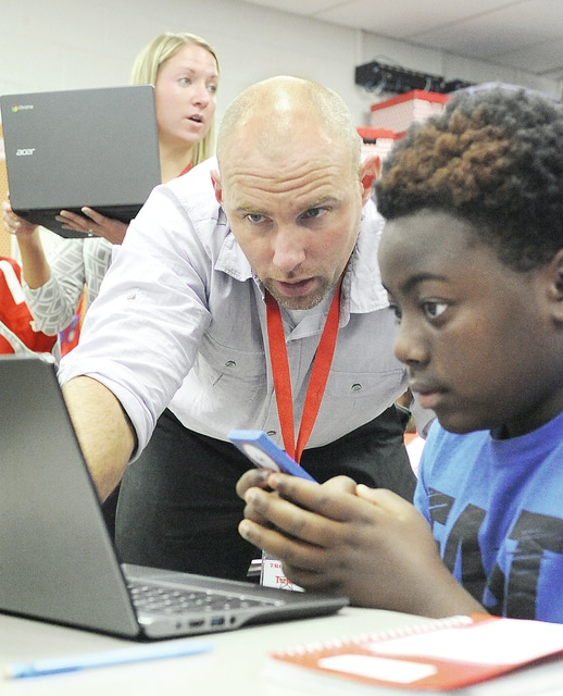 Anthony Weber | Troy Daily News Seventh-grade intervention specialiast Rory Hoke helps Jamarion Miller while working on a TENMARKS program Thursday in Alyssa Gibson's math class at Troy Junior High School.