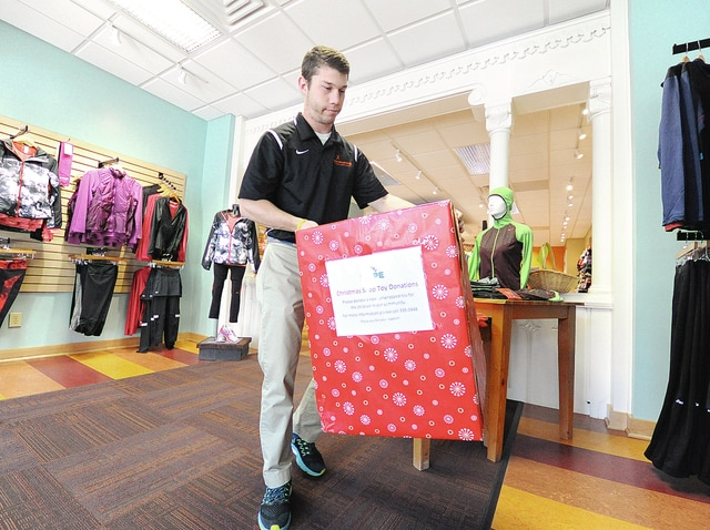 Anthony Weber | Troy Daily News Up and Running sales associate George Stubbs positions a Partners in Hope Christmas Shop donation box in the storefront area of the store Saturday in downtown Troy.