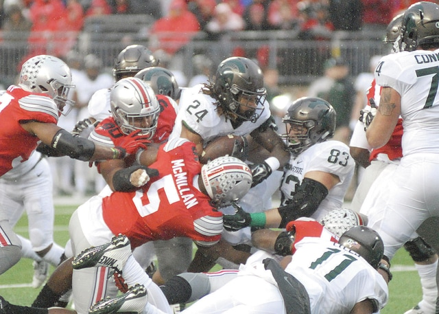 Anthony Weber | Troy Daily News Ohio State's Raekwon McMillan tackles Michigan's Gerald Holmes Saturday in Columbus.