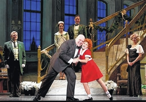 """Provided photo In this image released by Boneau/Bryan-Brown shows Gilgamesh Taggett as Oliver Warbucks, left, and Issie Swickle as Annie during a performance of the national tour of the musical """"Annie."""" Based on the beloved comic strip that debuted in 1924, """"Annie"""" first opened on Broadway in 1977 and ran for almost six years, fueled by songs including """"It's the Hard-Knock Life"""" and """"Tomorrow."""""""