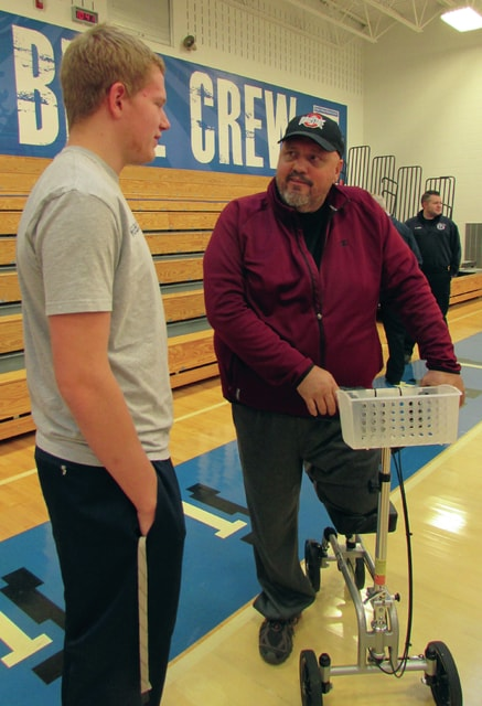 David Garrison thanks Miami East High School junior Jordan Crawford for helping him move away from his burning vehicle last September. Crawford, along with junior McKenna Bollinger, were honored by local officials during an assembly on Wednesday.