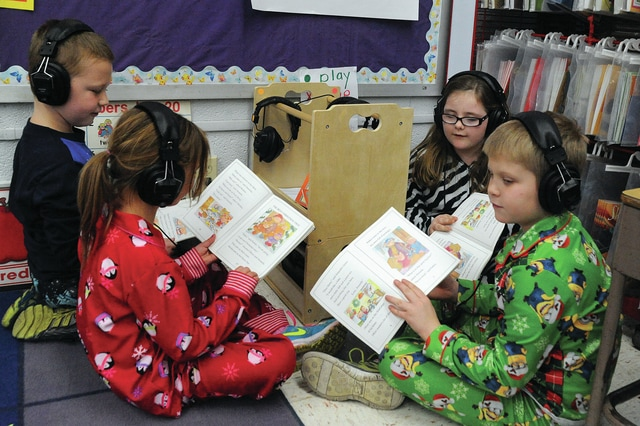 Mike Ullery | Daily Call Sophia Lankford, Trenton Havenar, Zoe Holfinger, and Elijah Brooks use the new listening center available in Gessner's first-grade class at Covington Elementary School.
