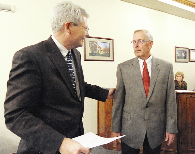 Anthony Weber | Troy Daily News City of Troy Law Director Grant Kerber shakes hands with John Terwilliger following a swearing in ceremony at City Hall Wednesday in Troy.