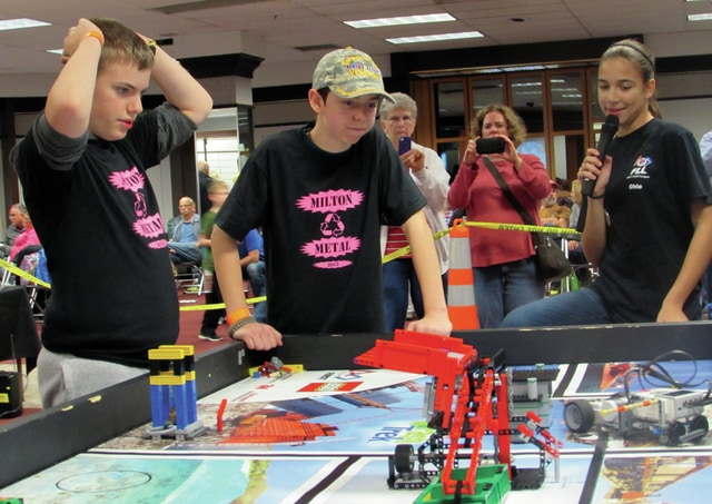 Milton Metal team members Dane Studebaker and Owen Reigelsperger watch as their robot completes a task as an emcee narrates the action for the audience.