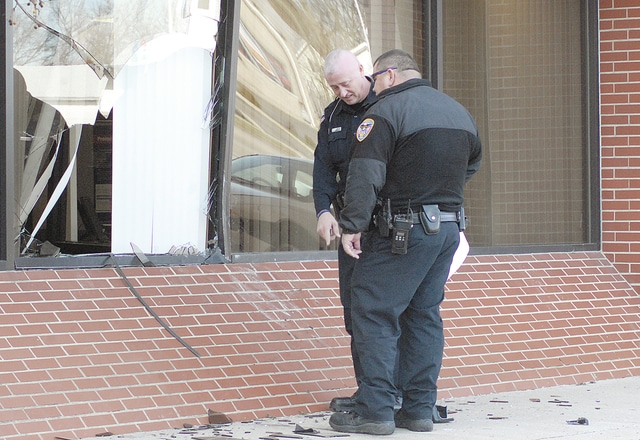 Anthony Weber | Troy Daily News Officers from the Troy Police Department including Officer Scott Gates and Officer Chris Madigan look over the destruction made by a motorist at the US Bank on West Main Street in Troy. Several glass windows were heavily damaged after a driver slammed into the front of the building at around 11 a.m. Wednesday.