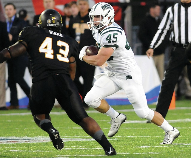 Ben Robinson | GoBuccs.com Covington High School graduate A.J. Ouellette (right), a sophomore running back at Ohio University, carries the ball for the Bobcats during the Camellia Bowl.