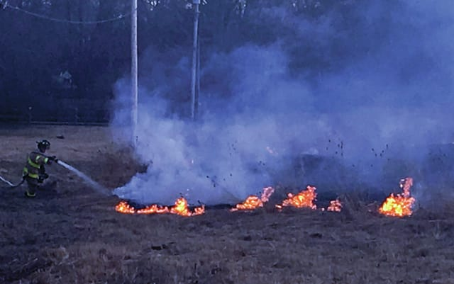 Contributed photos by Lisa Stetzel A Troy firefigher battles a field fire at the Hobart Urban Nature Preserve on Sunday evening.
